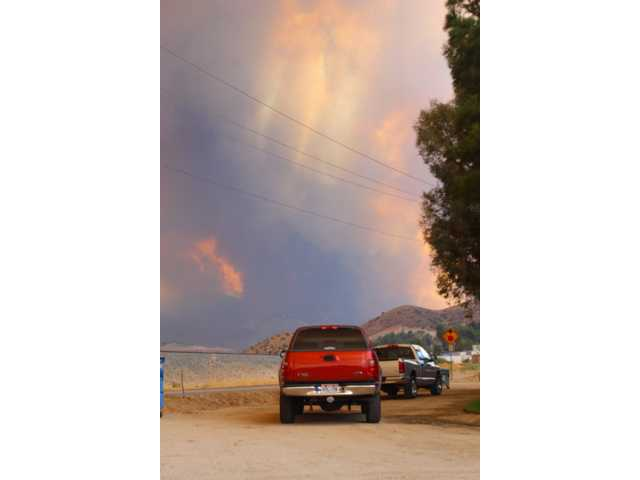 Motorists stop their pickup trucks on the side of the road in Acton to watch the Station Fire advance down the northeast slopes of the San Gabriel Mountains. Much of the rural town of Acton, located between the Antelope and Santa Clarita valleys, was evacuated early Sunday morning as the Station Fire, which began on the south side of the mountain range, moved northward.