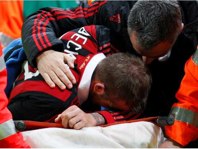 AC Milan English soccer star David Beckham leaves the pitch after being injured during the Serie A soccer match between AC Milan and Chievo at the San Siro stadium in Milan, Italy, Sunday, March 14, 2010. Beckham hobbled off with an apparent left leg injury in the closing minutes of AC Milan's game with Chievo. Italy's Sky TV reported that Beckham had probably torn his Achilles' tendon.