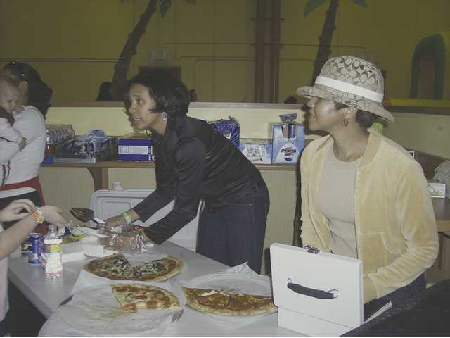 Mothers and members of the foundation committee of the Santa Clarita Valley/Antelope Valley chapter of Jack and Jill of America, Inc. Gwendolyn McDowell-Ferrell and Sara Mayo Rex sell pizza and soda, as well as other snacks to attendees of the Scooter's Jungle fundraiser held Jan. 8 in Valencia.