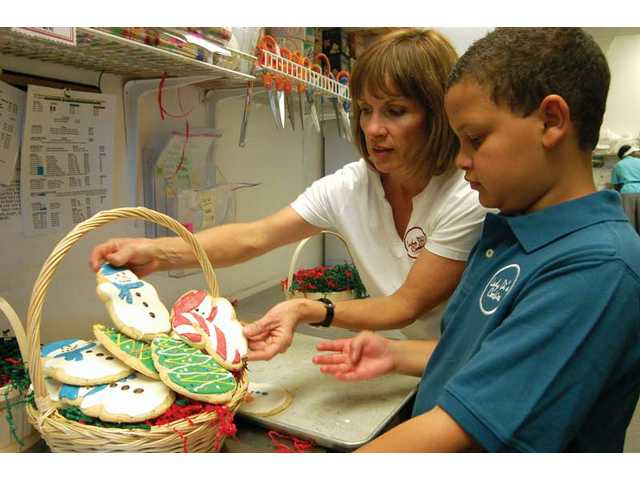 Lady Di's owner Diane Knight gets help from her son, Christopher, as they put together a package of decorated holiday cookies.