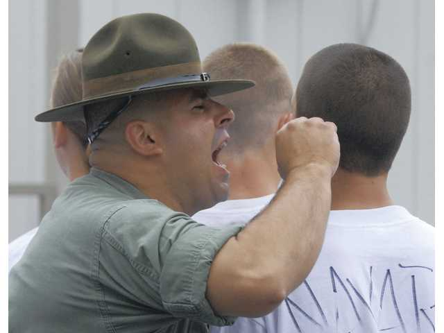 A VIDA program student is reprimanded by U.S. Marine volunteer Martin Lopez for wearing his pants below his hips at a boot camp on Saturday.