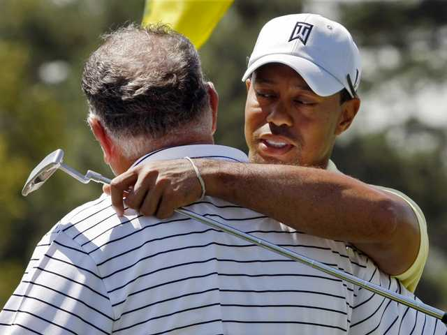 Tiger Woods, right, hugs Mark O'Meara on the 18th green at the conclusion of their practice round for the Masters golf tournament at Augusta National Golf Club on Tuesday, April 6, 2010, in Augusta, Ga. The tournament begins Thursday, April, 8.