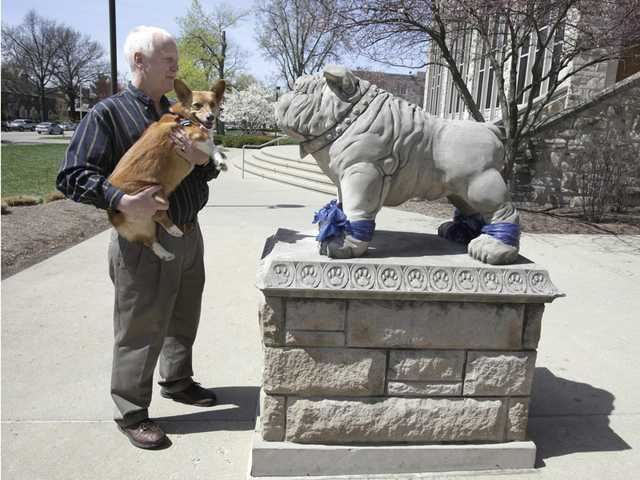 Jim Walsh of Overland Park, Kansas takes his dog Bella to see the Bulldog mascot statue on the campus of Butler University in Indianapolis on Sunday, April 4, 2010. Walsh and his wife Connie were in town to attend the NCAA college men's basketball championship weekend games. Butler faces Duke for the national championship on Monday night.