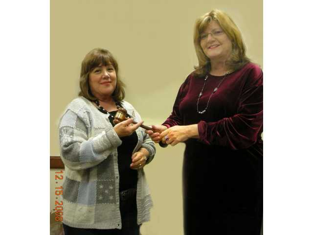Sandy Fisher, right, turns the Santa Clarita Artists' Association president's gavel over to incoming 2009 president Laurie Morgan.