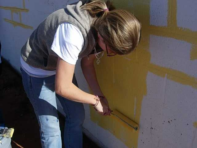 Melissa Selvastarts painting the preschool. Originally a bleak white and brown building, the kids turned the worn-out building into an eye-catching canary-yellow school.