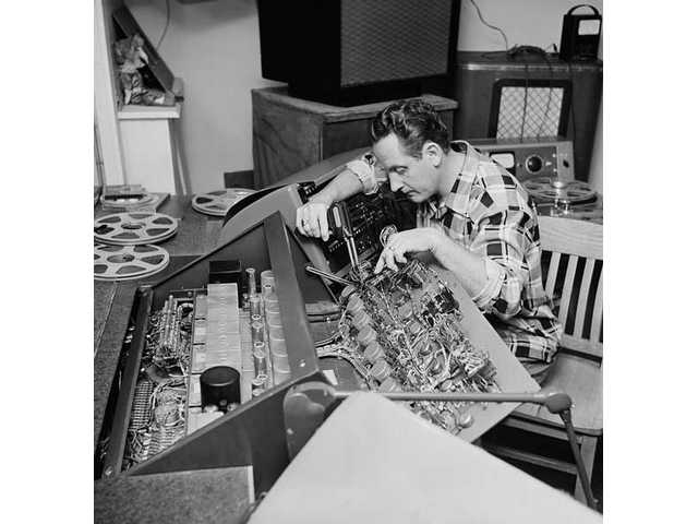 In this Dec. 20, 1963 file photo, Les Paul repairs one of the many control boards in the control room at his Mahwah, N.J., home. Paul, 94, the guitarist and inventor who changed the course of music with the electric guitar and multitrack recording and had a string of hits, died, Thursday, Aug. 13, 2009 in White Plains, N.Y