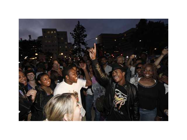 Marlon Russ, second right, sings to a Michael Jackson song in celebration of Jackson's life outside the UCLA Medical Center, in Los Angeles, Thursday, June 25, 2009.