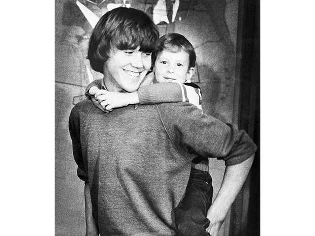 In this March 2, 1980 file photo, 5-year-old Timothy Lee White gets a piggy back ride from 14-year-old Steven Stayner at a news conference in Ukiah, Calif. White, the youngest victim and last survivor of a notorious California kidnapping saga whose rescue offered hope to parents of missing children, has died. He was 35.