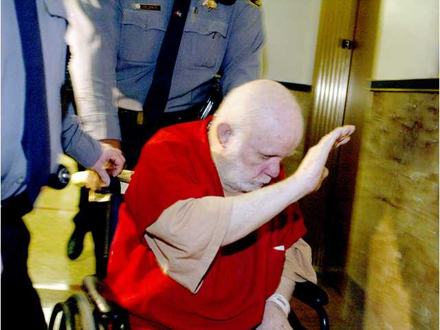 In this Feb 9, 2004 file photo, Kenneth Parnell, 72, tries to block his face from cameras as he is escorted from Alameda County Superior Court, in Oakland, Calif. Timothy White, the youngest victim and last survivor of a notorious California kidnapping saga whose rescue offered hope to parents of missing children, has died. He was 35.