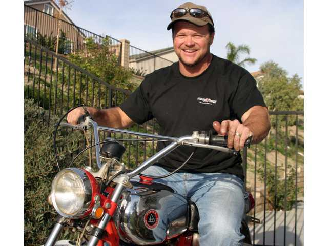 "Hollywood stuntman Jim Palmer of Valencia sits astride his vintage 1970 Hokada dirt bike. His book ""Stunt Adjustment"" offers a unique insider's look behind the scenes of big action TV and films."