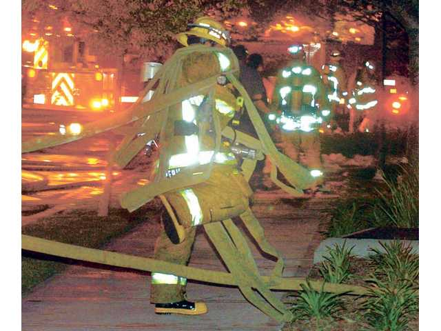 A firefighter steps over hose lines as colleagues battle the blaze.