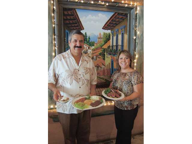 Raoul Bojorquez, left, and daughter Ivana hold up lamb chops and skirt steak, specialties at El Trocadero. The family-run restaurant has been in business for eleven years and holds a prime corner location in Old Town Newhall, which is currently being renovated.