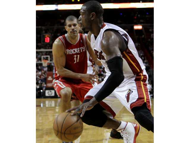 Miami Heat guard Dwyane Wade, right, drives to the basket as Houston Rockets guard Shane Battier (31) looks on in the third quarter during an NBA basketball game in Miami, Tuesday, Feb. 9, 2010.