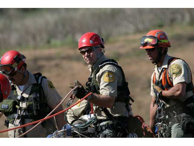 SCV Search and Rescue Team members Dave Christianson, left, Ken Wiseman, center, Tony Buttitta right, practice during a drill in the Santa Clarita Valley. Team members respond to diverse calls, ranging from evacuating civilians during fires to directing traffic following accidents to finding lost hikers.