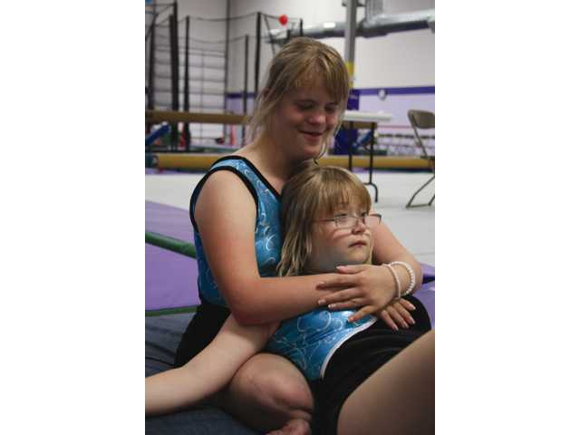 Santa Clarita Sharks members Monica Monheim and Melissa Grason take a break between competition performances during the Special Olympics meet at Gymnastics Unlimited on May 31.