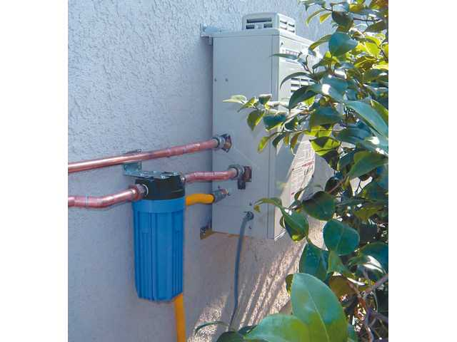 This is a tankless hot water heater, manufactured by Takagi. In this case, it has been installed on the outside of a home. However, the relatively small size of such systems (about 2.2 cubic feet) allows them to be installed in various locations.