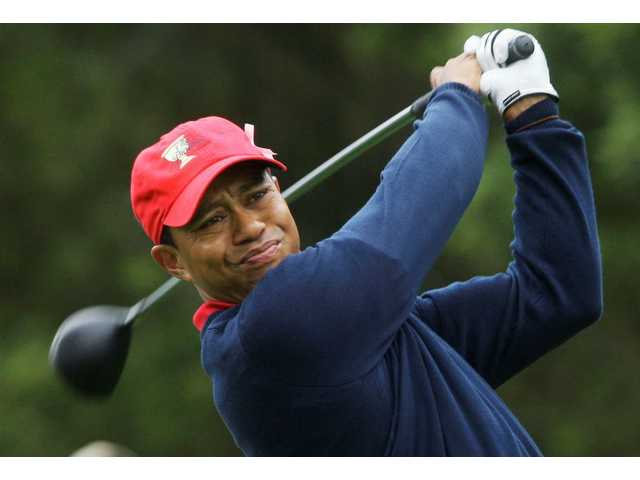 FILE - This Oct. 11, 2009, file photo shows Tiger Woods teeing off at the Presidents Cup at Harding Park Golf Course in San Francisco. Woods is back at home after a week of family counseling in Arizona and is trying to get back into a routine that includes golf and fitness, according to a person with knowledge of his schedule.