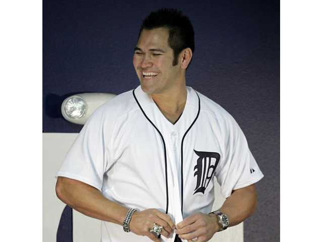 Detroit Tigers' Johnny Damon buttons his new jersey during a news conference at the team' spring training baseball practice facility, Monday, Feb. 22, 2010, in Lakeland, Fla. Damon signed a one-year contract with the Detroit Tigers.