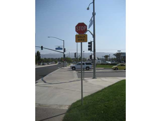 "One of the new cautionary ""WALK BIKE"" signs posted at the intersection of Cinema Drive and Valencia Boulevard is a part of the city's new Non-Motorized Transportation Plan."