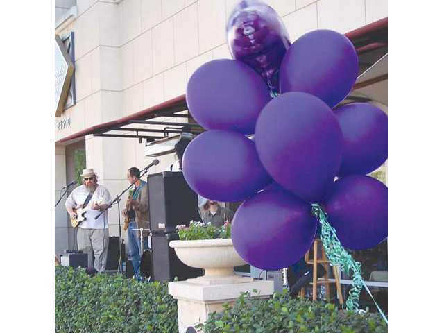 "A cluster of ""grape"" balloons waves in the breeze in front of the Vines restaurant."