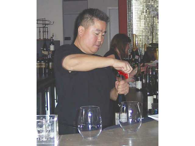 Lee's Wine Bistro owner Yoon Lee uncorks a bottle during The Wine Affair fundraiser to benefit the Sheila R. Veloz Breast Imaging Center.
