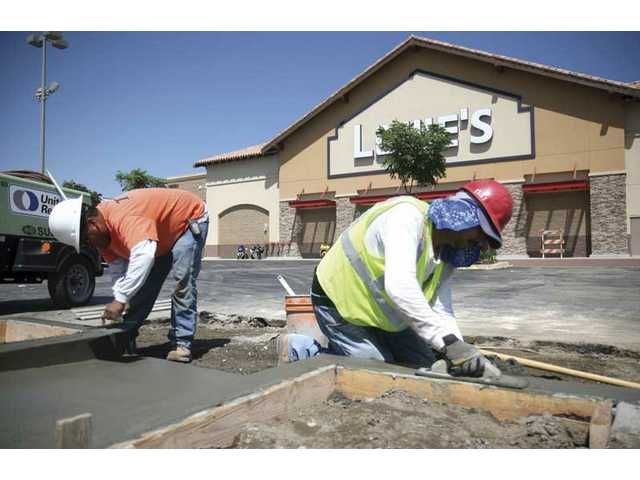 Jesus Sanchez, left, and Felipe Sosa, cement a sidewalk near the Lowes in Canyon Country on Thursday afternoon. The Plaza, including several major anchor stores, will open in phases in the coming months.