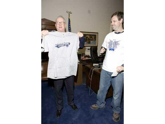 "U.S. Congressman Howard P. ""Buck"" McKeon (R-Santa Clarita)models a T-shirtshirt presented by Academy of the Canyons' senior class at his Washington, D.C., office Monday."
