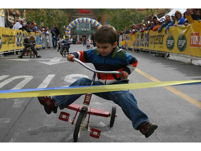 "Future Tour of California winner Sam Regez, 5, of Canyon Country, careens toward the finish line to win one of several heats of kids on trikes racing down Town Center Drive Saturday. ""Races were open to all kids. Keeps them busy and helps them get excited for what will happen later,"" said Mindy Herrera, city A&E clerk and tyke & trike wrangler."