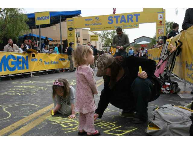 Tara Olsen of Santa Clarita and daughters Alexa, 4, and Ava, 2, inscribe a message of encouragement to people fighting cancer as the trio awaits the start of the Amgen Tour of California cycle race from Santa Clarita to Pasadena.