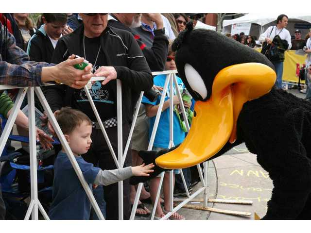 Daffy Duck and three-year-old Evan Wenz of Canyon Country slap five on Autograph Row before the start of the Amgen Tour of California's Stage 7 on Town Center Drive Saturday.