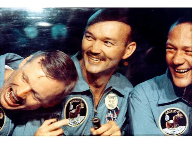Armstrong, Collins, and Aldrin smile through the window of the mobile quarantine van.