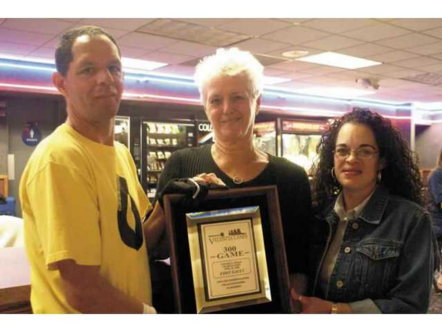 Eddie LeGault takes time out from bowling Thursday at Valencia Lanes and stands next to the award he received for his perfect game Apr. 22 with his mother Barbara Stefanavage and Valencia Lanes manager Yvette Boyer.