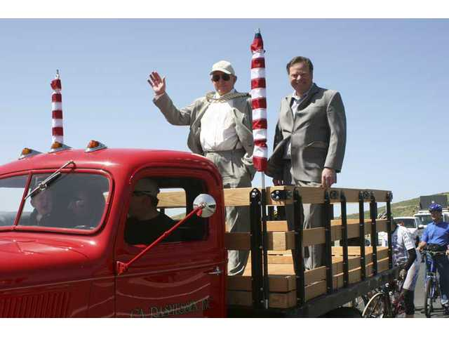 Centre Pointe developer Larry Rasmussen (left) and Santa Clarita City Councilman Bob Kellar ride in the bed of a restored stake bed truck. It was among the classic vehicles that were first to cross the bridge across the Santa Clara River after it was dedicated Saturday.
