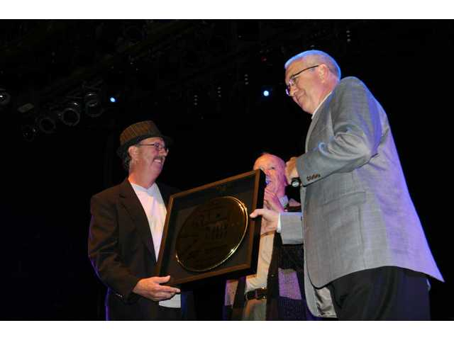 Jerry Keyawa (left) and his brother Stan (right) accept the golden drumhead plaque just presented them by Remo D. Belli, founder of Remo Inc., during the Professional Drum Shop's 50th birthday bash at the Avalon in Hollywood Saturday afternoon.