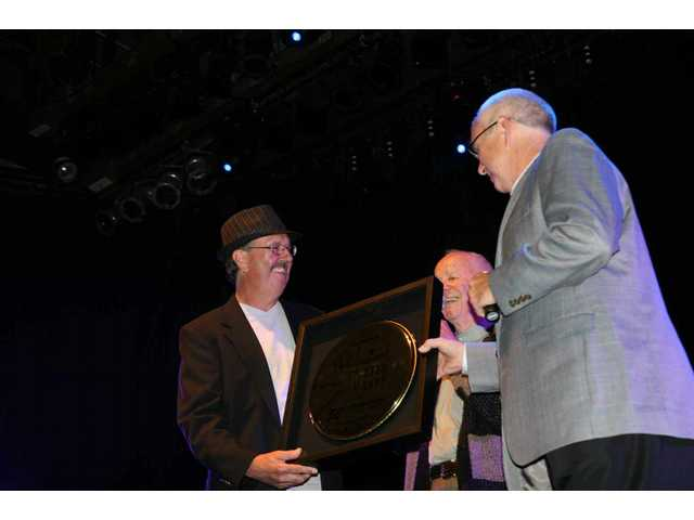 Remo Inc. founder Remo D. Belli (center) presents a golden drumhead to Professional Drum Shop owners Jerry (left) and Stan Keyawa at the shop's 50th anniversary party in Hollywood Saturday.