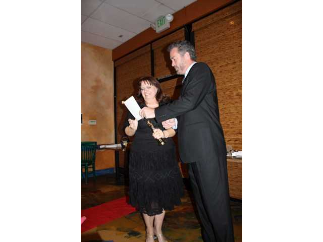 "Mary Gregory, left, is presented with her ""Oscar"" by actor James Edson of the Santa Clarita Valley. Gregory, of Mary's Schoolhouse, was installed as the 2009 president of the association."