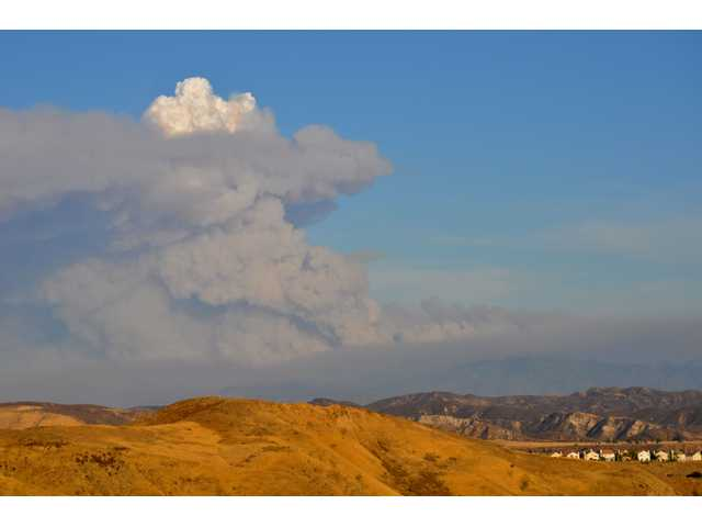 A huge plume of smoke capped with a heat-created artificial cumulonimbus cloud rises above Placerita Canyon in this view to the southeast from Castaic late Saturday afternoon. The Station Fire was headed through the Angeles National Forest over the Santa Clara divide separating the San Fernando and Santa Clarita valleys, and threatened to head northwest down the mountain toward Acton and the eastern SCV Saturday night. Firefighters announced a plan to make a stand near Acton at dawn Sunday.