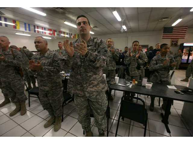 U.S. soldiers clap as they watch a television broadcast showing live pictures from Washington, D.C., unseen, of the inauguration of Barack Obama as the 44th president of the United States at the U.S. Camp Phoenix base in Kabul, Afghanistan on Tuesday, Jan. 20, 2009.