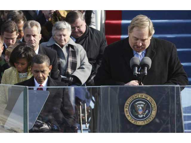 The Rev. Rick Warren, of the Saddleback Church in Lake Forest, Calif., gives the invocation as President-elect Barack Obama and his wife, Michelle, left, bow their heads during swearing-in ceremonies at the U.S. Capitol in Washington, D.C., Tuesday, Jan. 20, 2009.