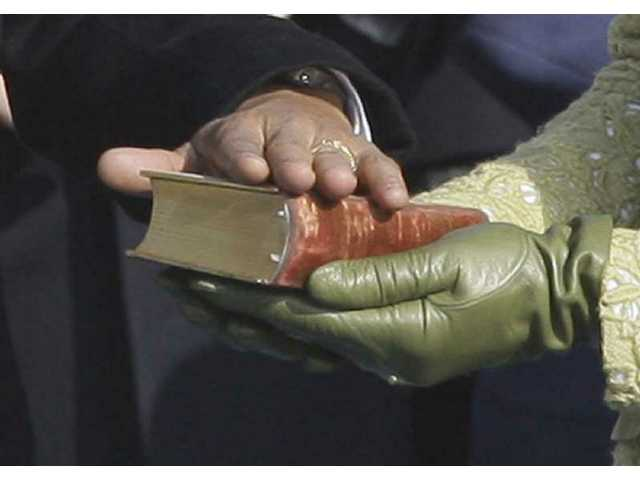 President Barack Obama rests his hand on President Lincoln's Inaugural Bible as his wife Michelle Obama holds it as he takes the oath of office at the U.S. Capitol in Washington, D.C., Tuesday, Jan. 20, 2009.
