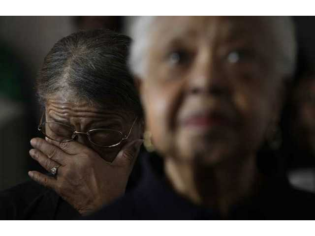 Ella Crawford, 73, left, wipes a tear while watching the inauguration of Barack Obama with Mary K. Jones, 78, right, at the Hannan House in Detroit, Tuesday, Jan. 20, 2009.