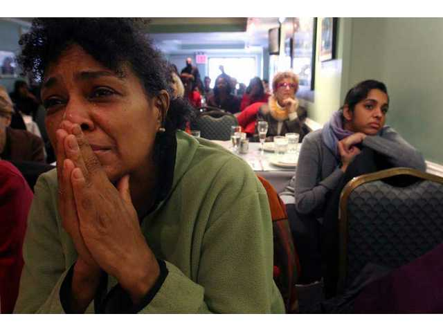 Michea Caye, of New York, left, reacts as she and others watch a live television broadcast of the inauguration of President Barack Obama at Sylvia's restaurant in New York's Harlem section Tuesday, Jan. 20, 2009.