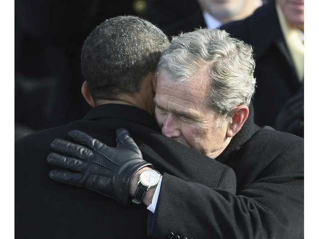 Former President George W. Bush, right, hugs President Barack Obama after Obama was sworn in at the U.S. Capitol in Washington, D.C., Tuesday, Jan. 20, 2009.