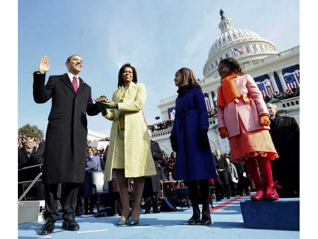 Barack Obama, left, takes the oath of office from Chief Justice John Roberts, not seen, as his wife Michelle, holds the Lincoln Bible and daughters Sasha, right and Malia, watch at the U.S. Capitol in Washington, D.C. Tuesday, Jan. 20, 2009.