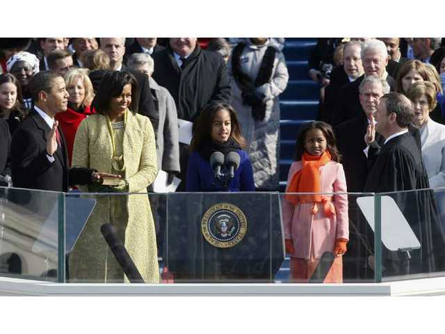 Barack Obama, left, joined by his wife Michelle, second from left, and daughters Malia, third from left, and Sasha, takes the oath of office from Chief Justice John Roberts to become the 44th president of the United States at the U.S. Capitol in Washington, D.C., Tuesday, Jan. 20, 2009.