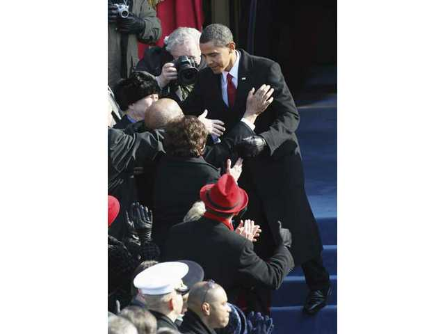 President-elect Barack Obama is greeted as he arrives for swearing-in ceremonies at the U.S. Capitol in Washington, D.C., Tuesday, Jan. 20, 2009.