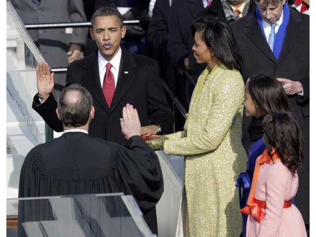 Barack Obama, left, joined by his wife Michelle, third from left, and daughters Sasha, fourth from left, and Malia, takes the oath of office from Chief Justice John Roberts to become the 44th president of the United States at the U.S. Capitol in Washington, D.C., Tuesday, Jan. 20, 2009.