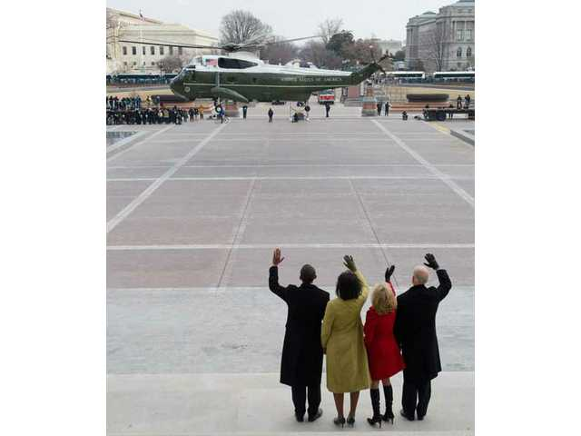 President Barack Obama waves alongside his wife, Michelle, Vice President Joe Biden and his wife, Jill, as former President George W. Bush and his wife, Laura, leave the U.S. Capitol by helicopter after Obama was sworn in as the 44th President in Washington, D.C., Tuesday, Jan. 20, 2009.