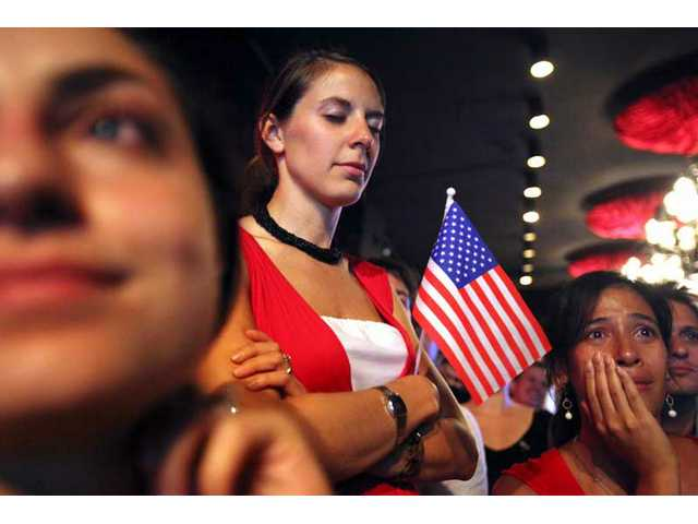 Ilana Lorge of Chicago, Ill., left, Joy Martinex of St. Augustine, Fla., center, and Jamie Stevens of Los Angeles, Calif., right, hold back their emotions as they gather at a party marking the inauguration of Barack Obama as President of the U.S., held on Wednesday, Jan. 21, 2009 in Singapore.