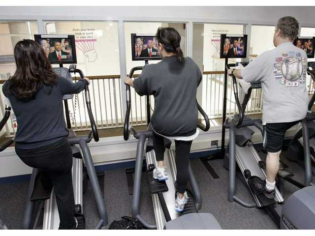 People workout at the Peninsula Jewish Community Center in Foster City, Calif., as they watch on television the presidential inauguration of President Barack Obama onTuesday, Jan. 20, 2009.